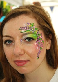 young woman face-painted with flowers