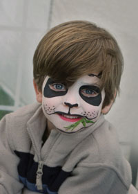 boy with face painted as panda bear